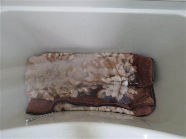 折りたたんで浴槽に入れたカーペットをシャワーのぬるま湯で濡らしながら洗う