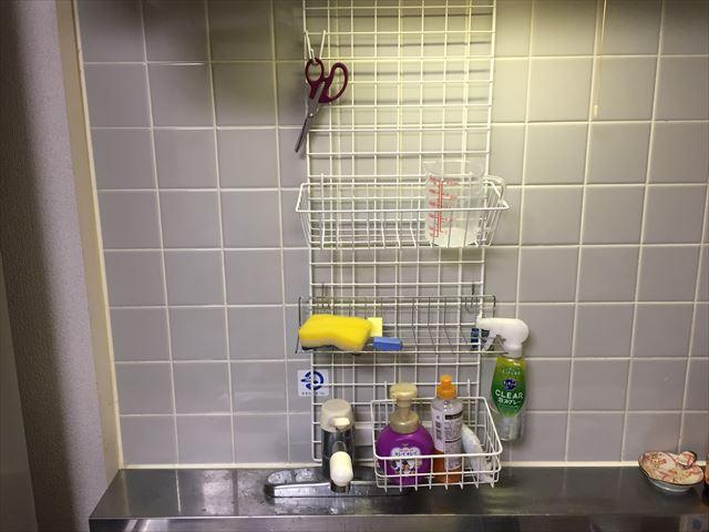 固定フックで吊られたワイヤーネットに籠やフックを取り付け収納棚の完成