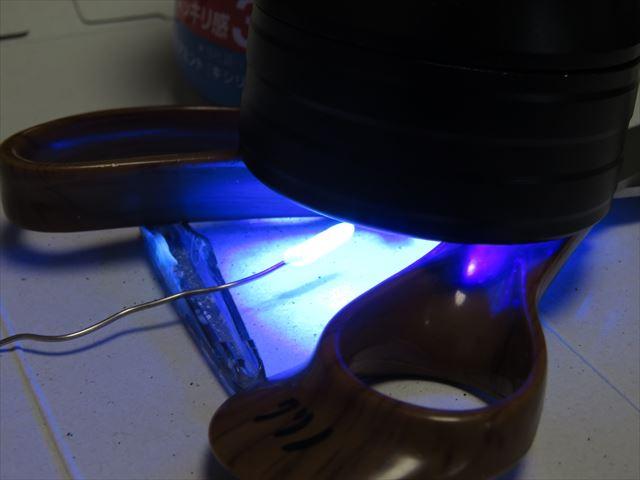 ゼムクリップに塗った光硬化パテを紫外線(UV)ライトで硬化させる