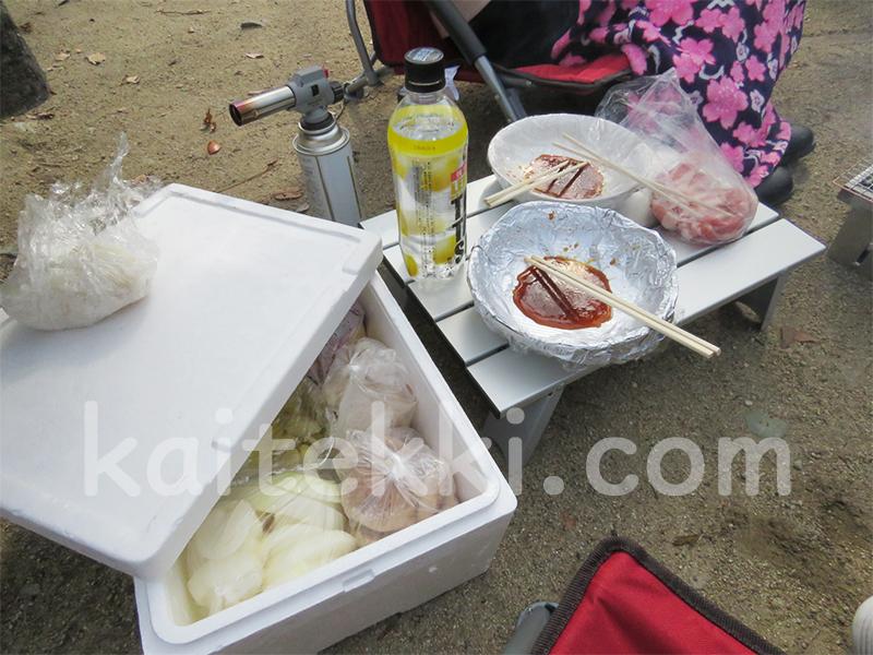 食材を入れた発泡スチロールケースと皿などを置くアルミテーブル